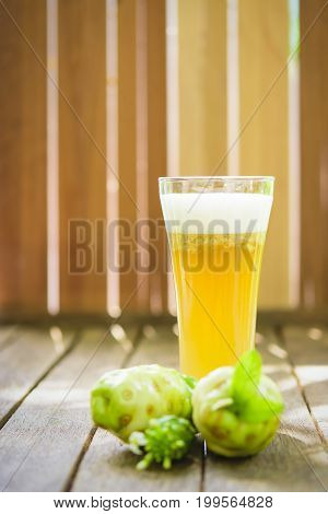 Noni fruit and noni juice and blossom on old wooden table.