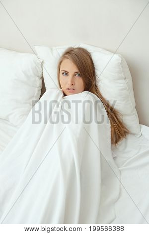 Blonde woman resting in bed at home in the bedroom. The constraining girl hides behind a blanket