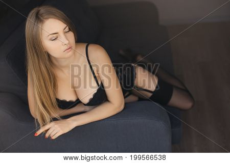 Picture of lovely blonde in black lingerie sitting on gray sofa