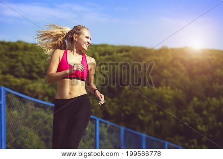 Smiling sport woman running in park. A beautiful slender blonde is engaged in sports. Stunning athletic blonde runs along the treadmill at dawn. The concept of a healthy lifestyle.
