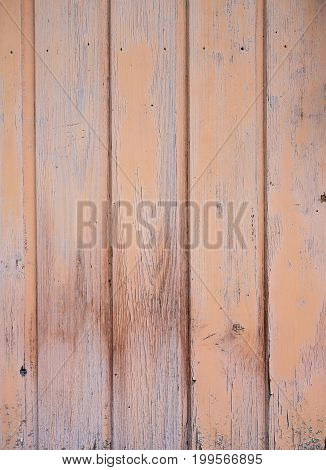 part of vertical wooden planks of shed wall with peeling pink or salmon paint