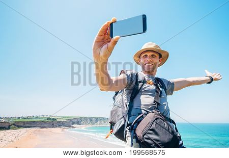 Backpacker traveler take a self photo with smartphone on beautiful ocean view
