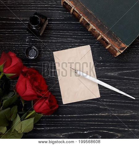Beautiful vintage background (blank sheet of paper with a dip pen ink-pot ancient book and three red roses on a worn black wooden background view from the top or flat lay)