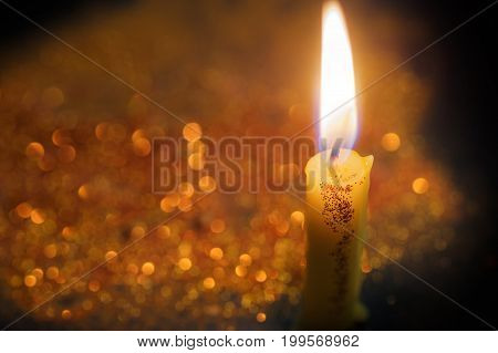 Selective focus on Candles light with gold bokeh backguond.