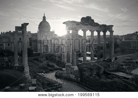 Rome Forum with ruins of ancient architecture at sunrise with sun ray. Italy.