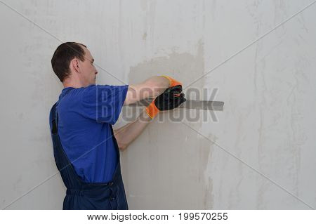 Master plasterer shpatlyuet wall with white putty