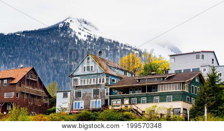 Large homes on hillside in Alaska with snow covered mountains in the background