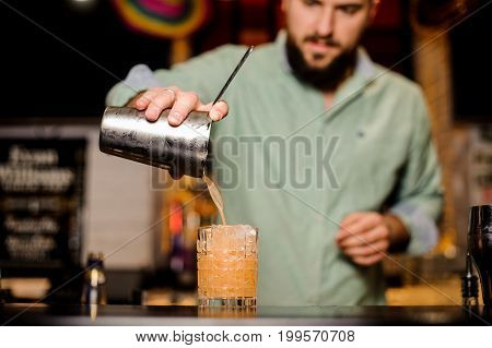 bartender making orange cocktail with serious face