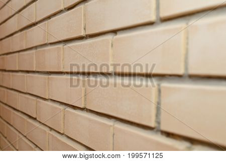 Neat brickwork made of beige bricks. View at an angle.