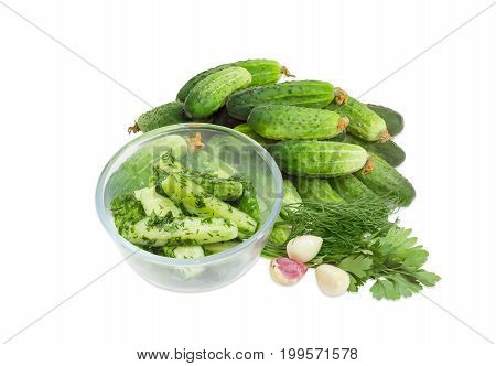 Lightly salted cucumbers in the glass bowl against of a pile of the freshly picked out cucumbers parsley dill and garlic on a white background