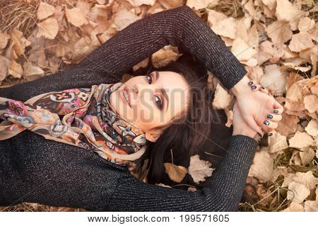 Autumn girl playing in city park. Portrait of an autumn woman lying over leaves and smiling outside in fall forest. Beautiful energetic mixed race Caucasian Asian young woman.