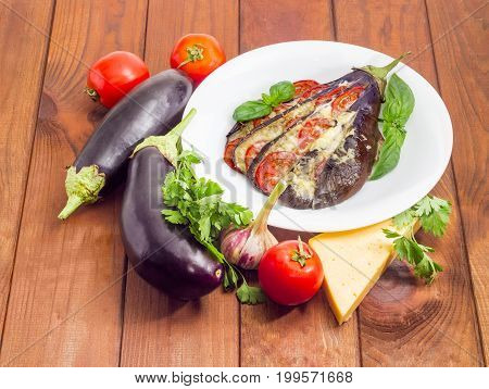 Baked eggplant stuffed with vegetables and cheese decorated with basil leaves on white dish and ingredients for its cooking beside on a surface of a dark wooden planks