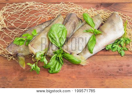 Several uncooked carcasses of the notothenia fish without of head and tail and twigs of basil and parsley on the fishing net on a dark wooden surface
