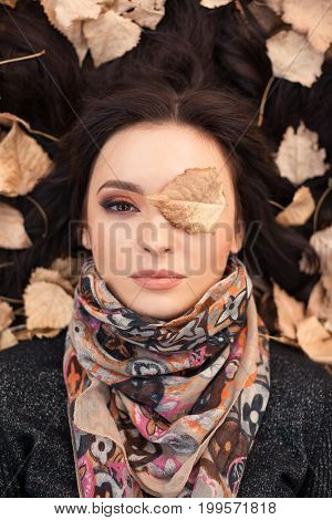 Autumn consept. Portrait of an autumn woman lying over leaves outside in fall forest. Beautiful mixed race Caucasian Asian young girl.