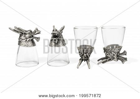 Set of four decorative glasses for vodka with a dragon head instead of a bottom isolated on a white background