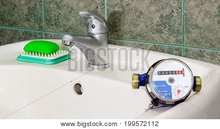 Not connected residential water meter for consumption measuring of a cold water on a wash basin on background of a water dripping from handle mixer tap and wall with green tiles