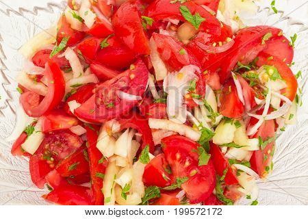 Background of the vegetable salad of a fresh sliced tomatoes white bell pepper onion and potherb in a glass salad bowl