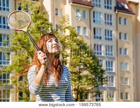 young beautiful woman playing badminton in the park on sunny summer day