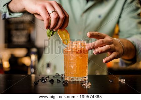 Bartender decorates cocktail with mint and slice from orange no face