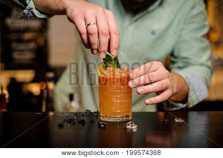 Bartender decorates cocktail with mint leaves no face