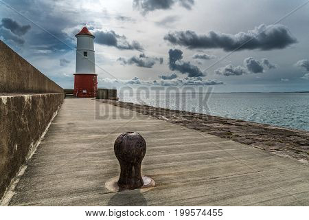 Lighthouse at the end of jetty and seawall Berwick upon Tweed Northumberland England under gathering storm clouds