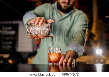 close up of bartender pouring the cocktail into the glass