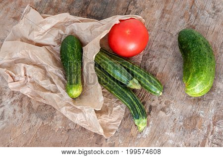 Tomato, Zucchini And Cucumber In Paper Bag On The Table