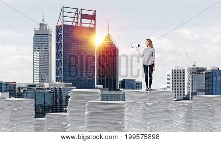 Woman in casual clothing standing on pile of documents with speaker in hand with cityscape and sunlight on background. Mixed media.