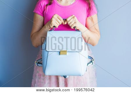 Close up stylish woman in pink skirt with blue bag. fashion concept