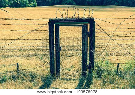Remains of iron curtain with door inside wire fence in Czech republic - retro style