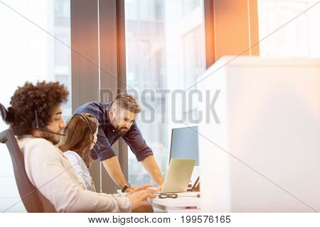 Young businessman using headset with colleagues discussing in background