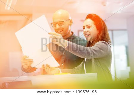 Smiling business people discussing over paperwork in office