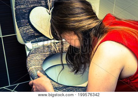 Young woman vomiting in the bathroom - morning sickness during pregnancy - retro style