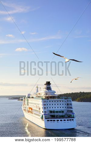 Cruise ship in the sea at sunset with flying gulls - Beautiful seascape. Copyspace composition