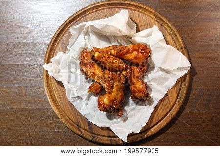 Chicken wings in hot sauce, specially prepared for beer. Chicken wings in hot sauce on a wooden plate.