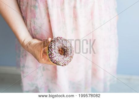 Close-up of woman holds chocolate donut cake. Unhealthy junk food concept on blue background.