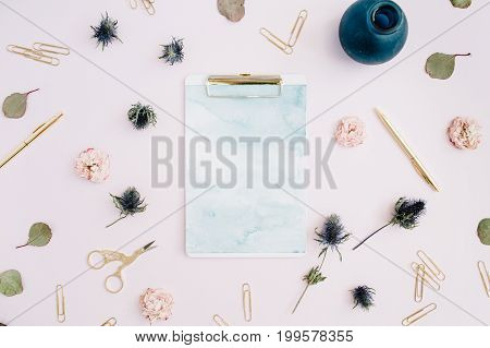 Flat lay of clipboard with space for text rose buds eucalyptus on pale pink background. Top view stylish mock up.