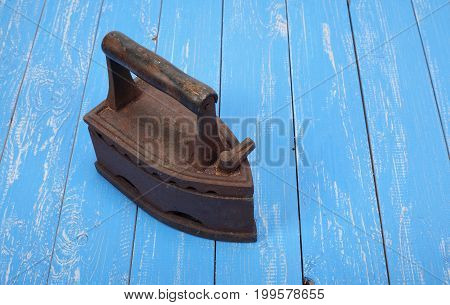 The old clothes charcoal iron on a blue wooden background.