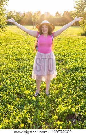 Free happy young woman raising arms watching the sun in the background at sunrise.