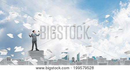 Businessman in suit standing among flying paper planes with speaker in hand and with skyscape on background. Mixed media.
