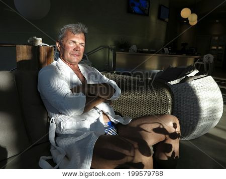 Respectable imposing man in a small white bathrobe rest after SPA procedures in a wicker armchair. He is relaxed happy calm. Life is good!