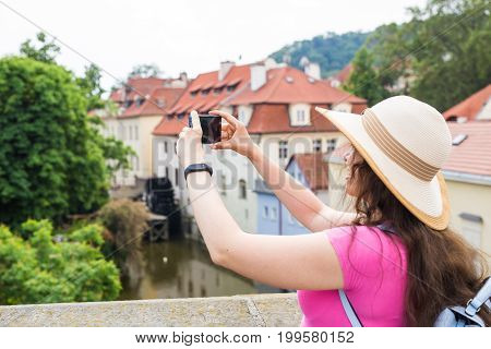 woman taking picture of Old Town in Prague with a smartphone
