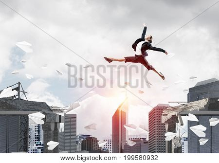 Business woman jumping over gap with flying paper planes in concrete bridge as symbol of overcoming challenges. Cityscape with sunlight on background. 3D rendering.