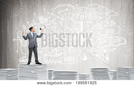 Businessman with speaker in hand standing on pile of documents with business-analytical information on background. Mixed media.