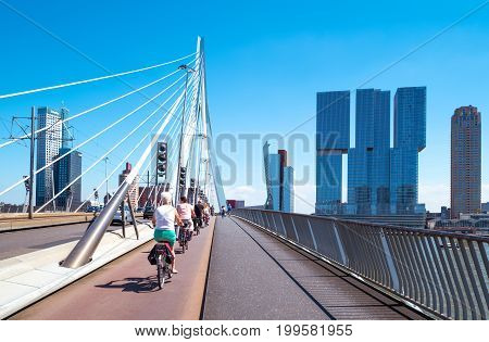 Rotterdam The Nederlands - July 18 2016: Cyclists crossing the Erasmus bridge on the Maas river with the De Rotterdam towers in the background
