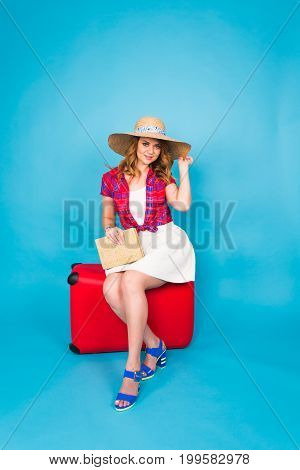 Young glamour woman with red suitcase. Travel, holidays and people concept.