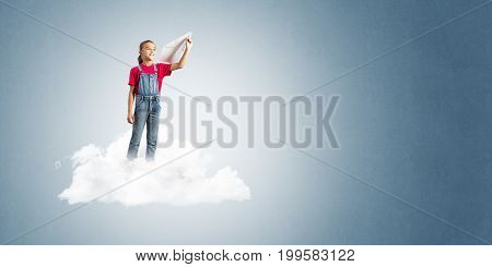 Cute kid girl standing on cloud and throwing paper plane
