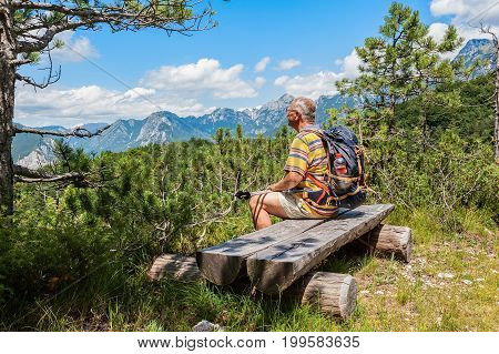 Mature hiker about 60 years old. Walker in rest . Rambler watching the Mountain panorama. Active retirement.