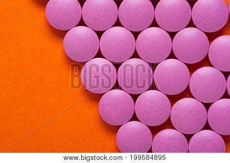 Group of pink medicine pills on orange background with copyspace. Medicaments background.