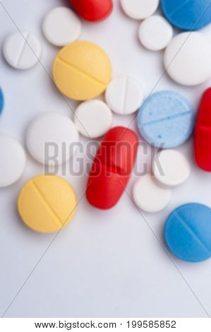 Macro shot of colorful medicaments, top view. Multicolored medical pills on white background with copyspace.